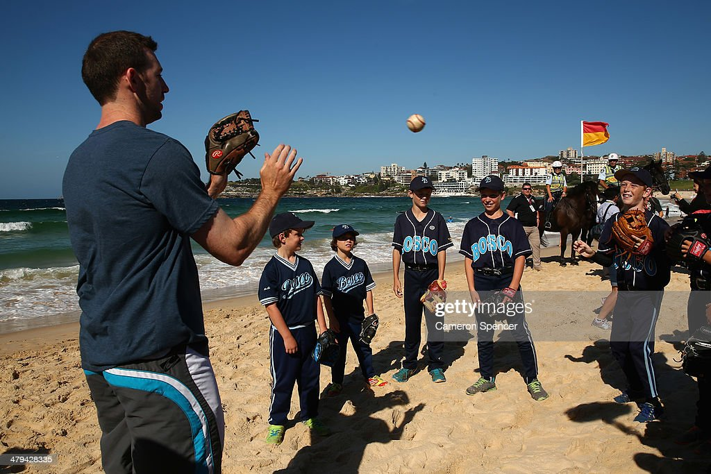 Mike Baxter of the Los Angeles Dodgers throws the ball with players from St John Bosco Little League during a Los Angeles Dodgers players visit at Bondi Beach on March 19, 2014 in Sydney, Australia.