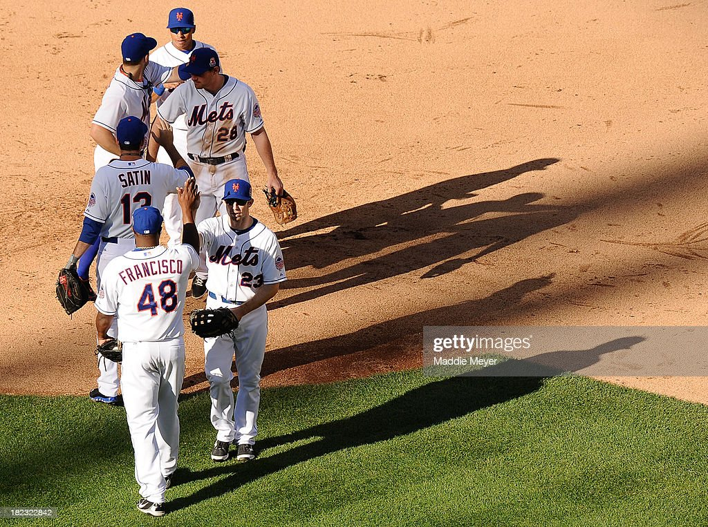 Mike Baxter #23 of the New York Mets, Frank Francisco #48, Josh Satin #13, and Daniel Murphy #28 celebrate after the game against the Milwaukee Brewers at Citi Field on September 29, 2013 in New York City. The Mets defeat the Brewers 3-2.