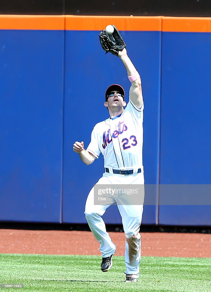 Mike Baxter #23 of the New York Mets makes the catch but runner Starling Marte of the Pittsburgh Pirates scores on the play on May 12, 2013 at Citi Field in the Flushing neighborhood of the Queens borough of New York City.