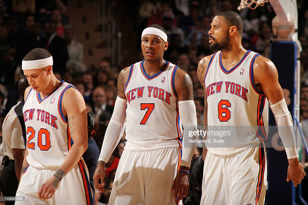 Mike Bibby #20, Carmelo Anthony #7 and Tyson Chandler #6 of the New York Knicks walk back to the bench during the game against the Boston Celtics on April 17, 2012 at Madison Square Garden in New York City.
