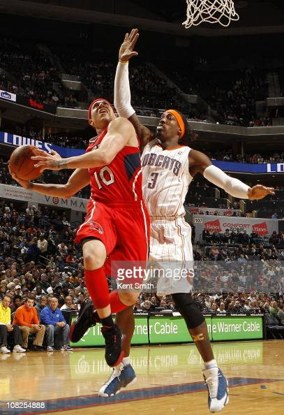 Mike Bibby of the Atlanta Hawks shoots against Gerald Wallace of the Charlotte Bobcats on January 22 2011 at Time Warner Cable Arena in Charlotte...