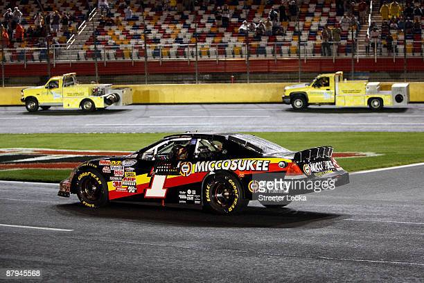 Mike Bliss driver of the Miccosukee Indian Gaming Resort Chevrolet waits in his car on pit road in a rain delay during the NASCAR Nationwide Series...