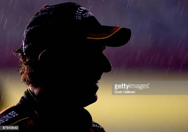 Mike Bliss driver of the Miccosukee Indian Gaming Resort Chevrolet stands on the grid in a rain delay during the NASCAR Nationwide Series CARQUEST...
