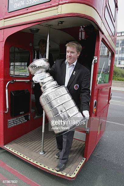 Mike Bolt of the Hockey Hall of Fame walks off the tour bus with the Stanley Cup as it goes on a tour of London on April 19 2006 in London England...