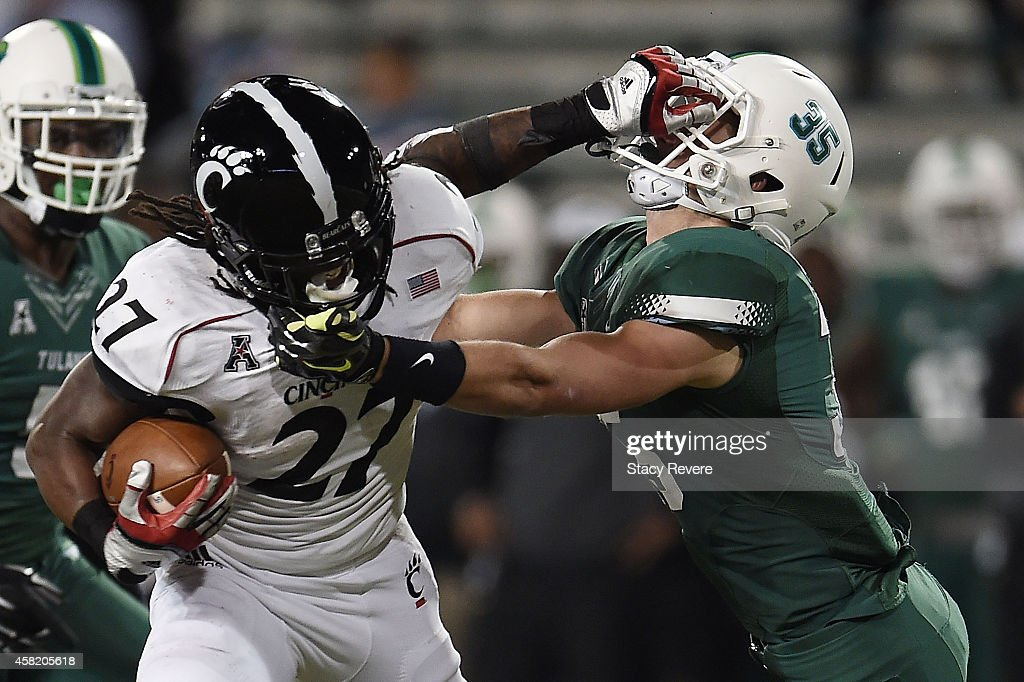 Mike Boone #27 of the Cincinnati Bearcats avoids a tackle by Sam Scofield #35 of the Tulane Green Wave during the fourth quarter of a game at Yulman Stadium on October 31, 2014 in New Orleans, Louisiana.