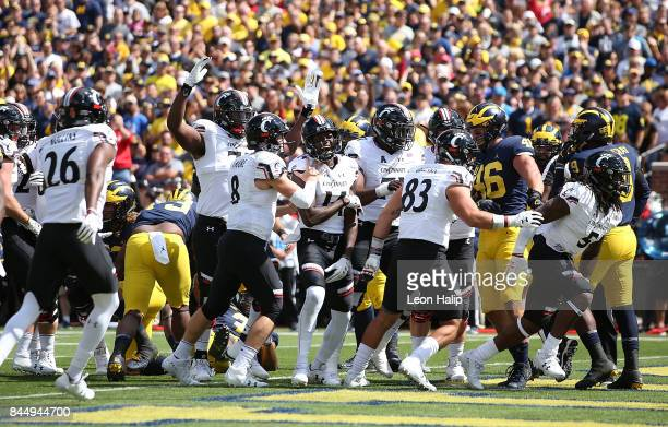 Mike Boone of the Cincinnati Bearcats scores on a one yard run and celebrates with his team during the first quarter of the game against the Michigan...