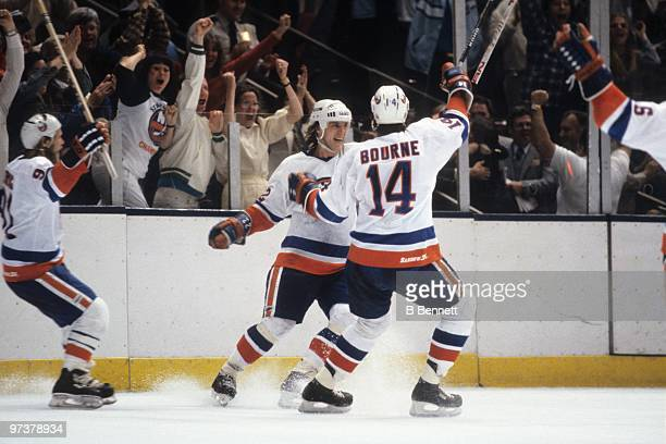 Mike Bossy of the New York Islanders celebrates his gamewinning goal with teammates Butch Goring and Bob Bourne in the first overtime of Game One of...