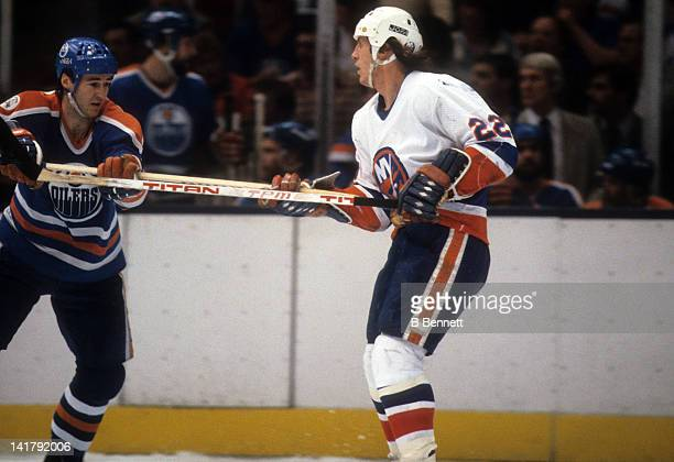 Mike Bossy of the New York Islanders grabs the stick of Kevin Lowe of the Edmonton Oilers during the 1983 Stanley Cup Finals in May 1983 at the...