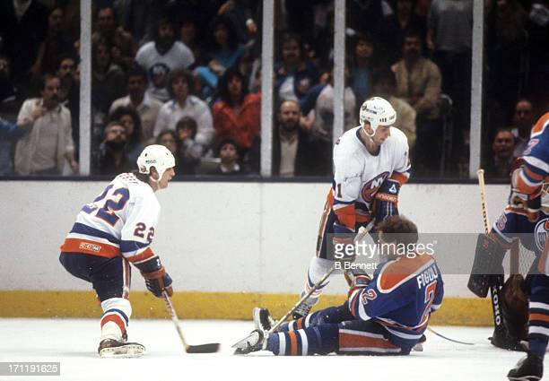 Mike Bossy of the New York Islanders has his shot blocked by Lee Fogolin of the Edmonton Oilers as Brent Sutter of the Islanders looks for a rebound...