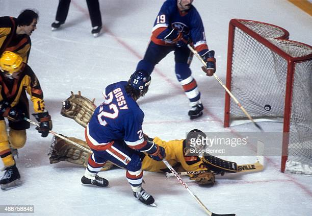 Mike Bossy of the New York Islanders scores the game winning goal as his teammate Bryan Trottier makes sure it's in as goalie Richard Brodeur of the...
