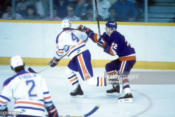 Mike Bossy of the New York Islanders tries to grab Kevin Lowe of the Edmonton Oilers during the 1984 Stanley Cup Finals in May 1984 at the Northlands...