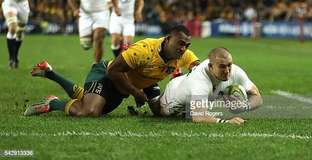 Mike Brown of England holds off Tevita Kuridrani to score their second try during the International Test match between the Australian Wallabies and...