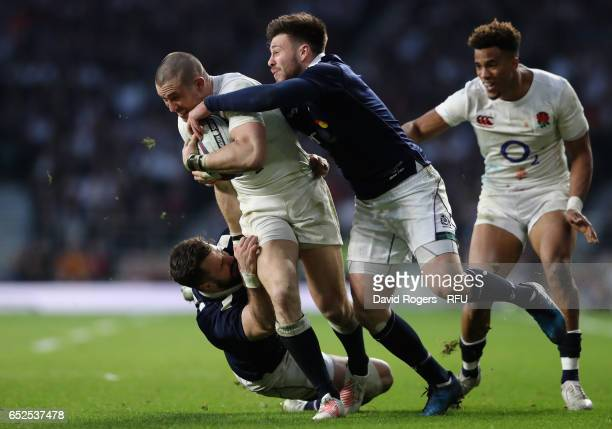 Mike Brown of England is tackled by Ali Price and Alex Dunbar during the RBS Six Nations match between England and Scotland at Twickenham Stadium on...