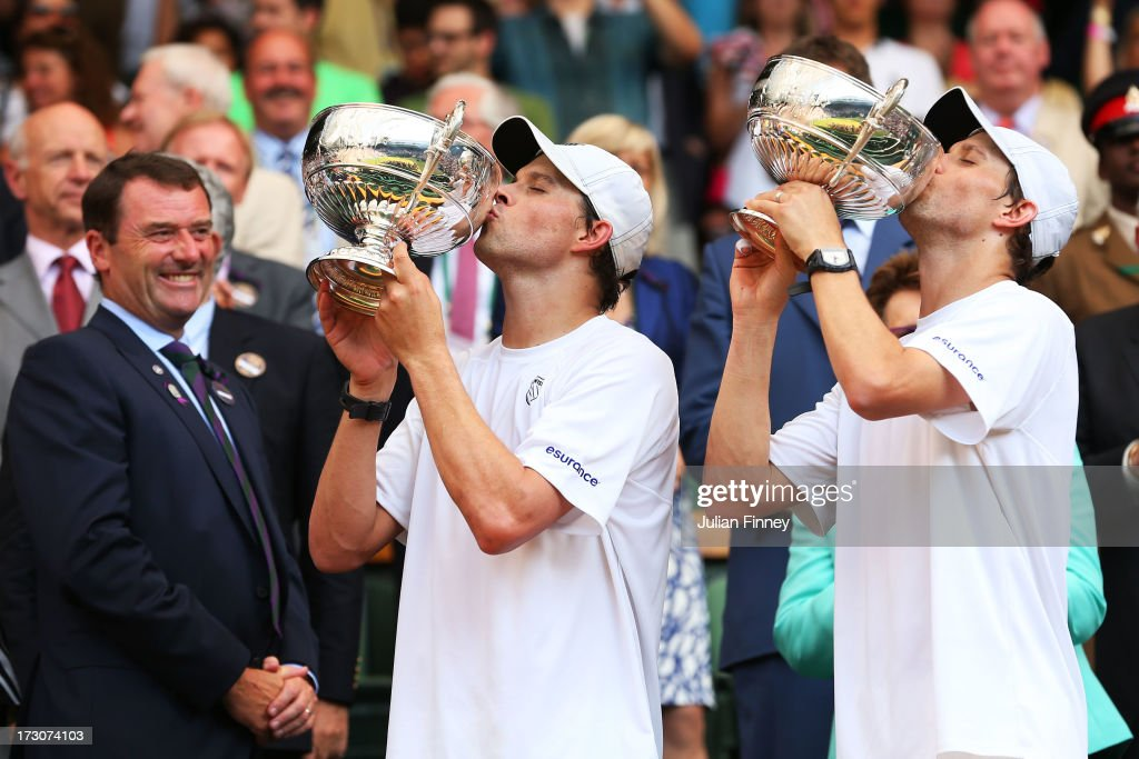 Mike Bryan and Bob Bryan of the United States of America kiss the Gentlemen's Doubles Trophies next to AELTC Chairman Philip Brook following their victory in the Gentlemen's Doubles final match against Ivan Dodig of Croatia and Marcelo Melo of Brazil on day twelve of the Wimbledon Lawn Tennis Championships at the All England Lawn Tennis and Croquet Club on July 6, 2013 in London, England.