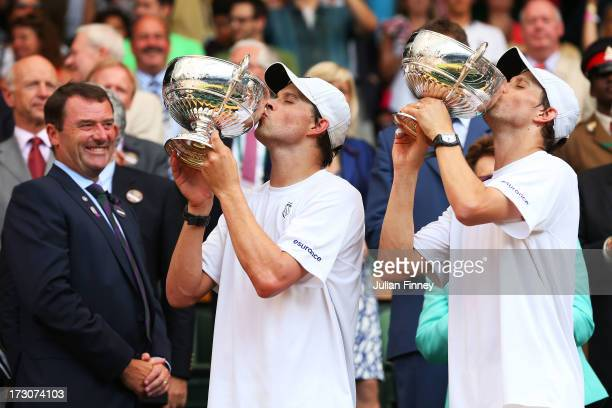 Mike Bryan and Bob Bryan of the United States of America kiss the Gentlemen's Doubles Trophies next to AELTC Chairman Philip Brook following their...