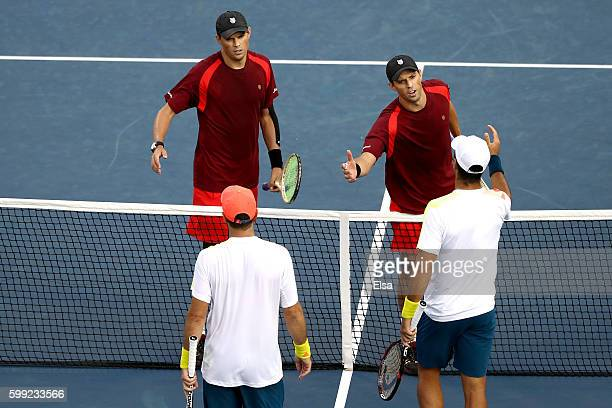 Mike Bryan and Bob Bryan of the United States shake hands after they defeated David Marrero and Fernando Verdasco of Spain during their third round...