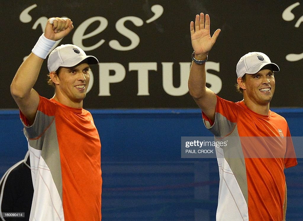 Mike Bryan (R) and his brother Bob of the US celebrate after their victory over the Netherland's Robin Haase and Igor Sibling during the men's doubles final on day 13 of the Australian Open tennis tournament in Melbourne early on January 27, 2013.