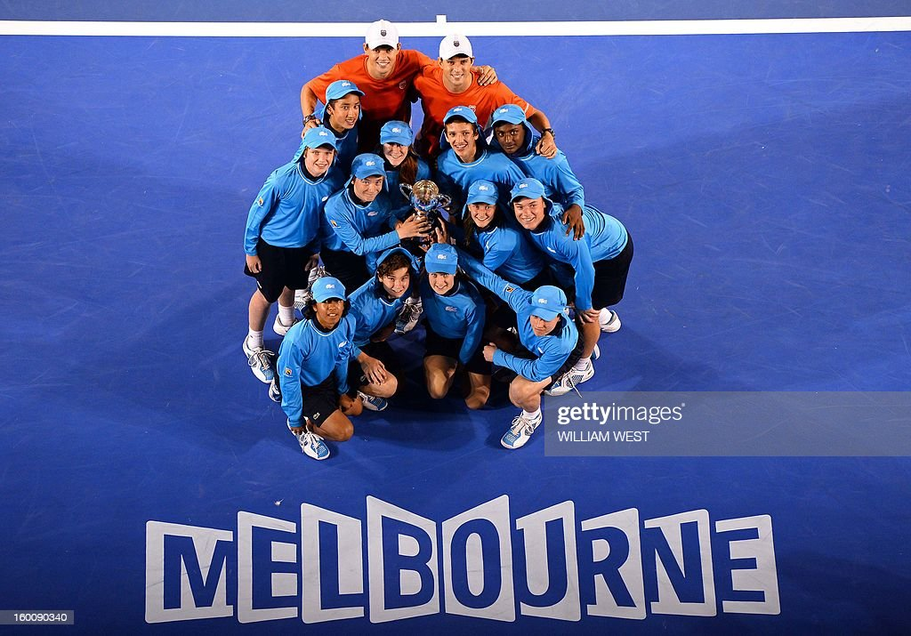 Mike Bryan (L) and his brother Bob of the US pose with ball children after their victory over the Netherland's Robin Haase and Igor Sibling during the men's doubles final on day 13 of the Australian Open tennis tournament in Melbourne early on January 27, 2013.