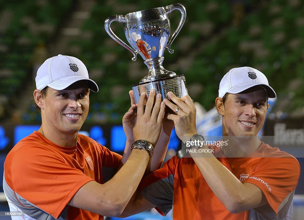 Mike Bryan (L) and his brother Bob of the US pose with the winners trophy after their victory over the Netherland's Robin Haase and Igor Sibling during the men's doubles final on day 13 of the Australian Open tennis tournament in Melbourne early on January 27, 2013. AFP PHOTO / PAUL CROCK IMAGE STRICTLY RESTRICTED TO EDITORIAL USE - STRICTLY NO COMMERCIAL USE