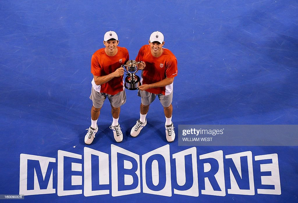 Mike Bryan (L) and his brother Bob of the US pose with the winner's trophy after their victory over the Netherland's Robin Haase and Igor Sibling during the men's doubles final on day 13 of the Australian Open tennis tournament in Melbourne early on January 27, 2013. AFP PHOTO / WILLIAM WEST IMAGE STRICTLY RESTRICTED TO EDITORIAL USE - STRICTLY NO COMMERCIAL USE