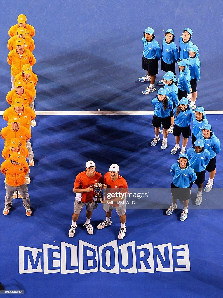 Mike Bryan (L) and his brother Bob of the US pose with the winner's trophy after their victory over the Netherland's Robin Haase and Igor Sibling during the men's doubles final on day 13 of the Australian Open tennis tournament in Melbourne early on January 27, 2013.