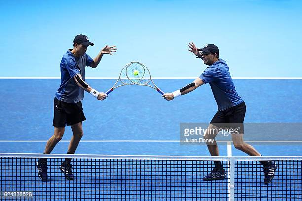 Mike Bryan of the United States and Bob Bryan of the United States attempt to volley at the net during their men's doubles semifinal match against...