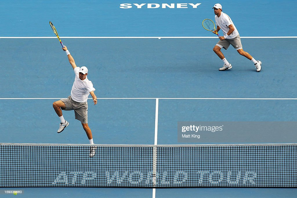 Mike Bryan (L) of USA plays a smash at the net playing with Bob Bryan (R) against Max Mirnyi of Belarus and Horia Tecau of Romania during day seven of the Sydney International at Sydney Olympic Park Tennis Centre on January 12, 2013 in Sydney, Australia.