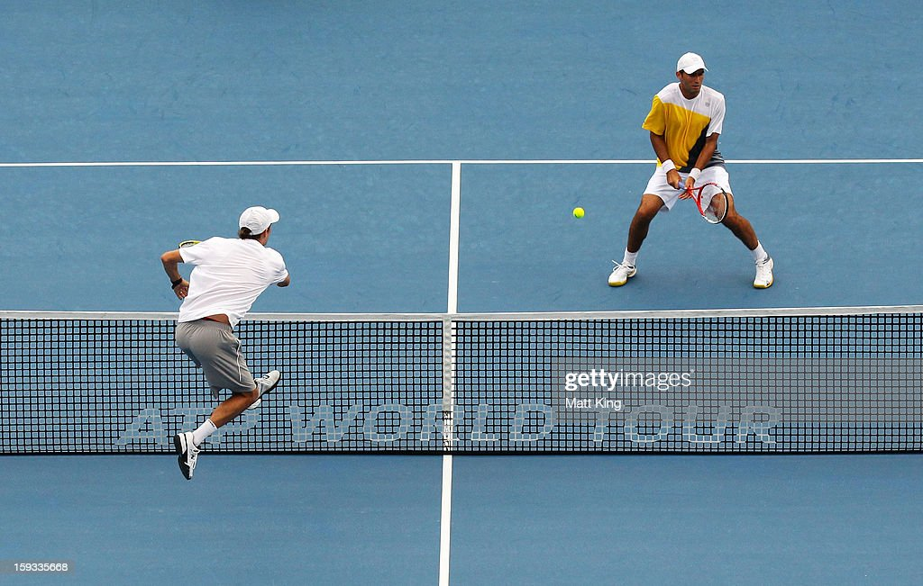 Mike Bryan (L) of USA plays a smash at the net playing with Bob Bryan against Max Mirnyi of Belarus and Horia Tecau (R) of Romania during day seven of the Sydney International at Sydney Olympic Park Tennis Centre on January 12, 2013 in Sydney, Australia.