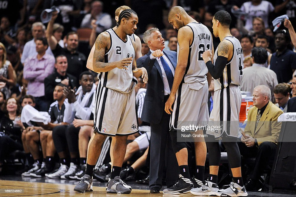 Mike Budenholzer, assistant coach of the San Antonio Spurs, speaks with Tim Duncan #21 and Kawhi Leonard #2 before resuming play against the Memphis Grizzlies in Game Two of the Western Conference Finals during the 2013 NBA Playoffs on May 21, 2013 at the AT&T Center in San Antonio, Texas.