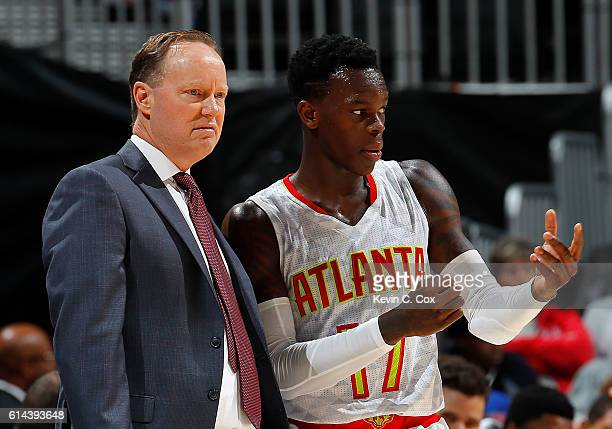 Mike Budenholzer of the Atlanta Hawks converses with Dennis Schroder during the game against the Detroit Pistons at Philips Arena on October 13 2016...
