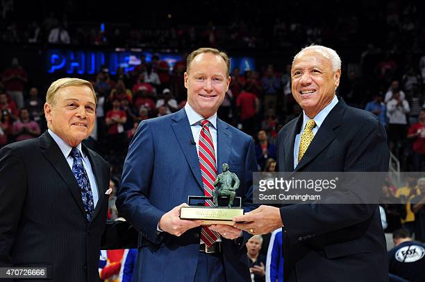 Mike Budenholzer of the Atlanta Hawks receives the 2015 NBA Coach of the Year Award from former Atlanta Hawks coaches Miek Fratello and Lenny Wilkens...