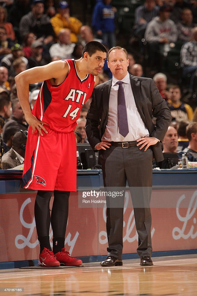 Mike Budenholzer of the Atlanta Hawks shares a word with Gustavo Ayon #14 during the game against the Indiana Pacers at Bankers Life Fieldhouse on February 18, 2014 in Indianapolis, Indiana.