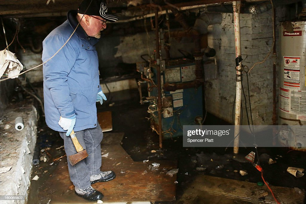 Mike Burke looks at his flooded and frozen basement in the Rockaways following Hurricane Sandy on January 25, 2013 in New York City. Burke has no heat do to a destroyed boiler. Three months after Sandy devastated parts of New York and New Jersey, hundreds of residents are still without electricity and heat and depend on churches and charities to meet their basic needs. This past week saw some of the coldest temperatures of the winter hit parts of New York.