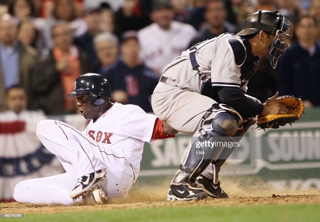 Mike Cameron #23 of the Boston Red Sox slides home safely past Jorge Posada #20 of the New York Yankees on April 4, 2010 during Opening Night at Fenway Park in Boston, Massachusetts.