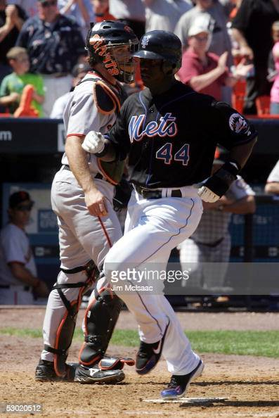 Mike Cameron of the New York Mets scores his teams third run after a base hit from teammate Mike Piazza in the fifth inning as catcher Mike Matheny...