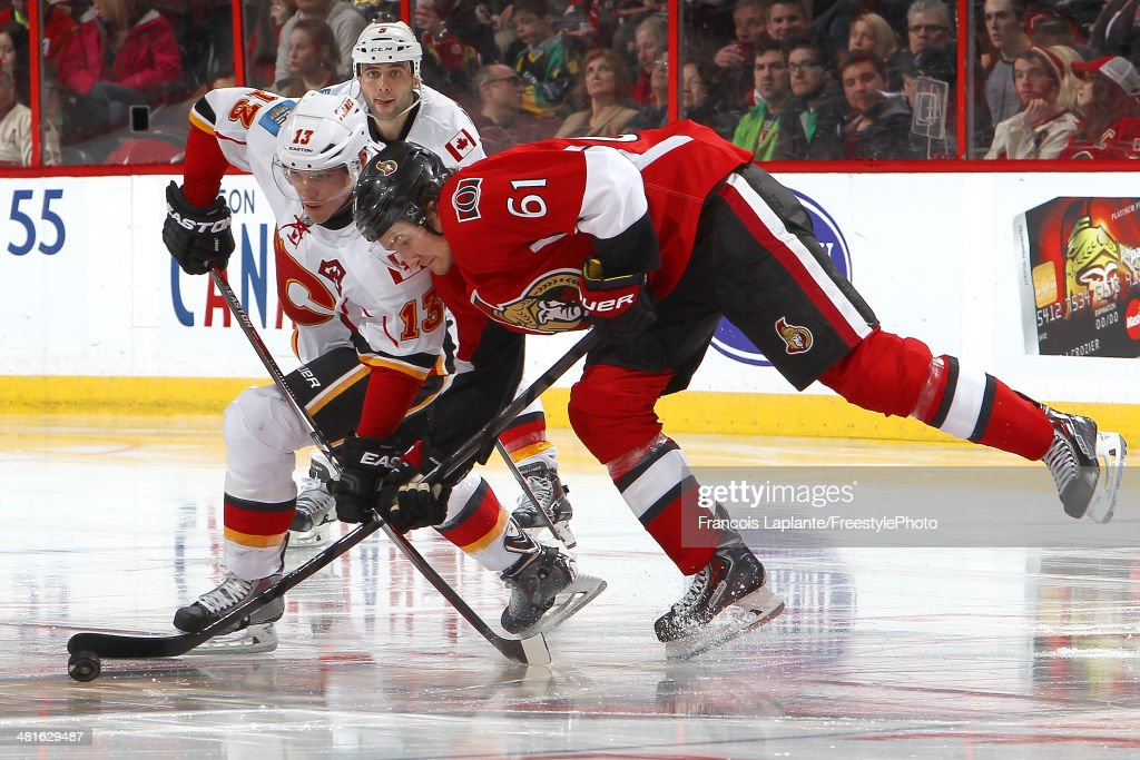 <a gi-track='captionPersonalityLinkClicked' href=/galleries/search?phrase=Mike+Cammalleri&family=editorial&specificpeople=634009 ng-click='$event.stopPropagation()'>Mike Cammalleri</a> #13 of the Calgary Flames battles for a loose puck against Mark Stone #61 of the Ottawa Senators during an NHL game at Canadian Tire Centre on March 30, 2014 in Ottawa, Ontario, Canada.