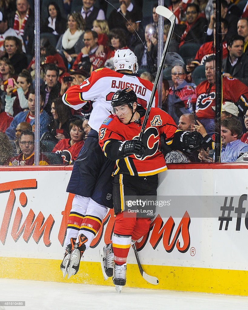 Mike Cammalleri #13 of the Calgary Flames collides with Nick Bjugstad #27 of the Florida Panthers during an NHL game at Scotiabank Saddledome on November 22, 2013 in Calgary, Alberta, Canada. The Flames defeated the Panthers 4-3 in shootout.