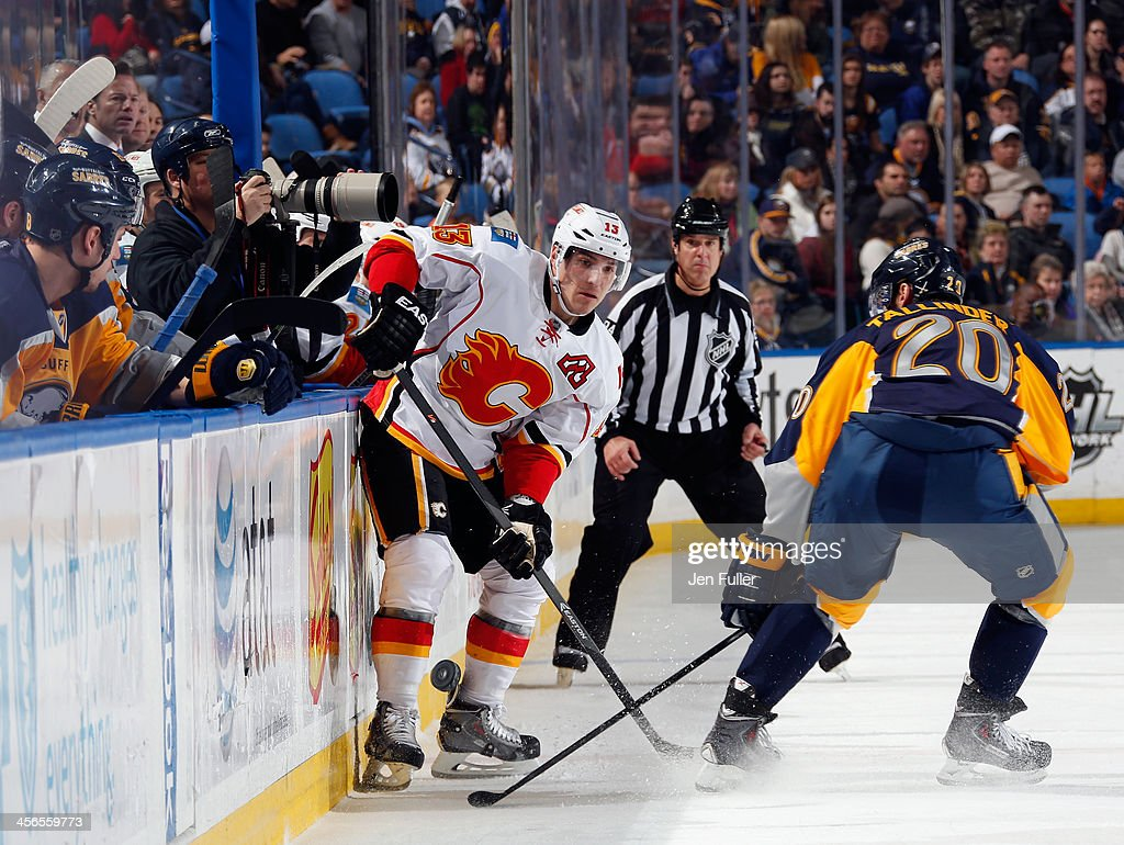 Mike Cammalleri #13 of the Calgary Flames passes the puck along the boards against Henrik Tallinder #20 of the Buffalo Sabres at First Niagara Center on December 14, 2013 in Buffalo, New York.