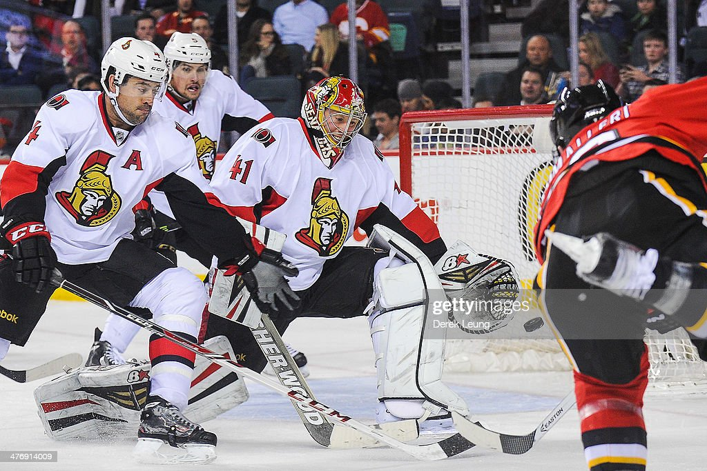 <a gi-track='captionPersonalityLinkClicked' href=/galleries/search?phrase=Mike+Cammalleri&family=editorial&specificpeople=634009 ng-click='$event.stopPropagation()'>Mike Cammalleri</a> #13 of the Calgary Flames shoots the puck past the defence of <a gi-track='captionPersonalityLinkClicked' href=/galleries/search?phrase=Craig+Anderson&family=editorial&specificpeople=211238 ng-click='$event.stopPropagation()'>Craig Anderson</a> #41 of the Ottawa Senators during an NHL game at Scotiabank Saddledome on March 5, 2014 in Calgary, Alberta, Canada. The Flames defeated the Senators 4-1.