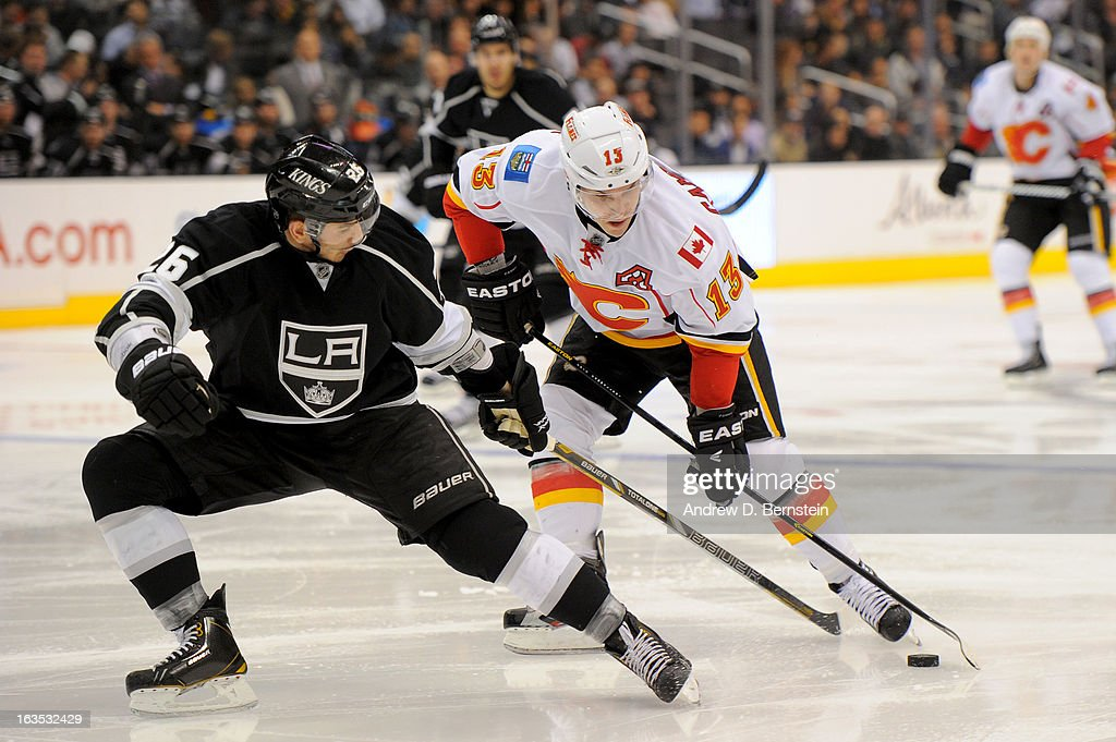 Mike Cammalleri #13 of the Calgary Flames skates with the puck against Slava Voynov #26 of the Los Angeles Kings at Staples Center on March 11, 2013 in Los Angeles, California.