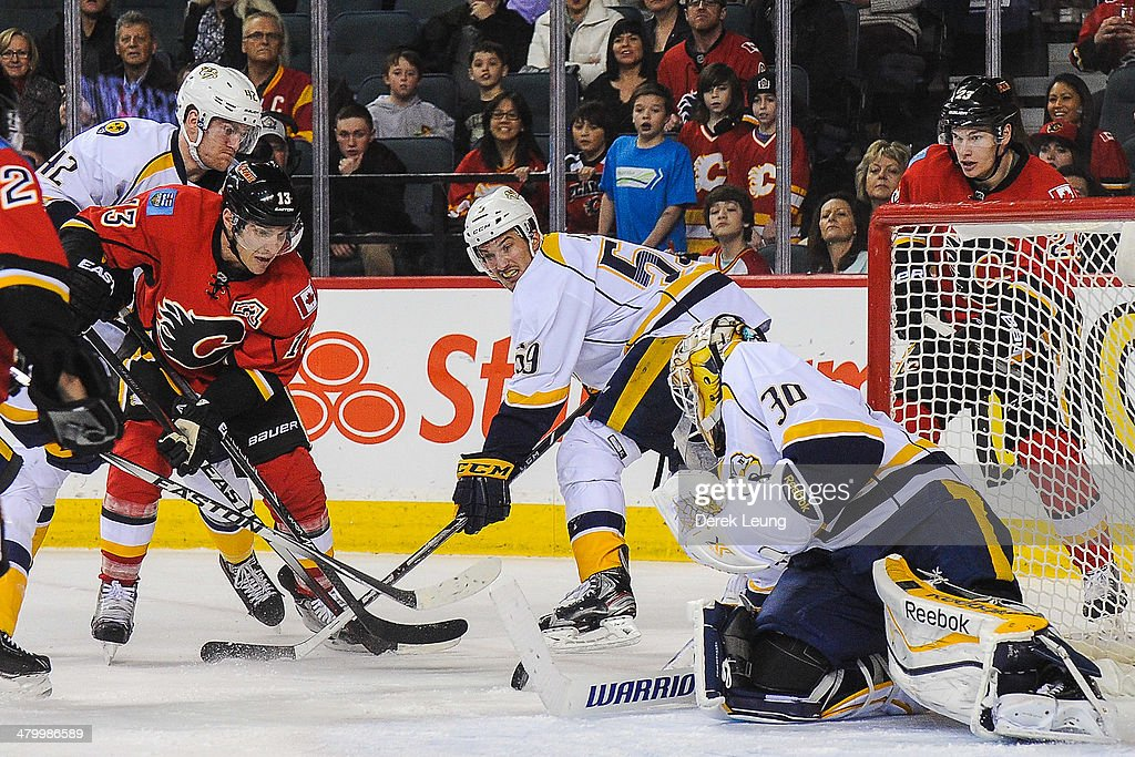 <a gi-track='captionPersonalityLinkClicked' href=/galleries/search?phrase=Mike+Cammalleri&family=editorial&specificpeople=634009 ng-click='$event.stopPropagation()'>Mike Cammalleri</a> #13 of the Calgary Flames takes a shot against <a gi-track='captionPersonalityLinkClicked' href=/galleries/search?phrase=Carter+Hutton&family=editorial&specificpeople=6872781 ng-click='$event.stopPropagation()'>Carter Hutton</a> #30 of the Nashville Predators during an NHL game at Scotiabank Saddledome on March 21, 2014 in Calgary, Alberta, Canada. The Predators defeated the Flames 6-5.
