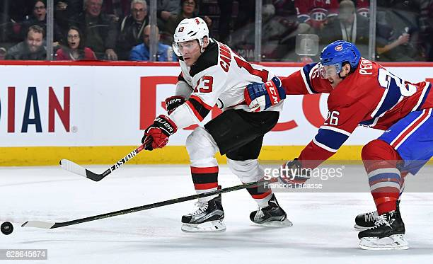 Mike Cammalleri of the New Jersey Devils passes the puck against pressure from Jeff Petry of the Montreal Canadiens in the NHL game at the Bell...