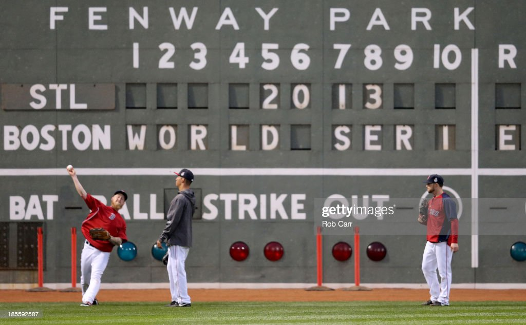 Mike Carp (L) #37 of the Boston Red Sox throws the ball in the outfield during team workout in the 2013 World Series Media Day at Fenway Park on October 22, 2013 in Boston, Massachusetts. The Red Sox host the Cardinals in Game 1 on October 23, 2013.