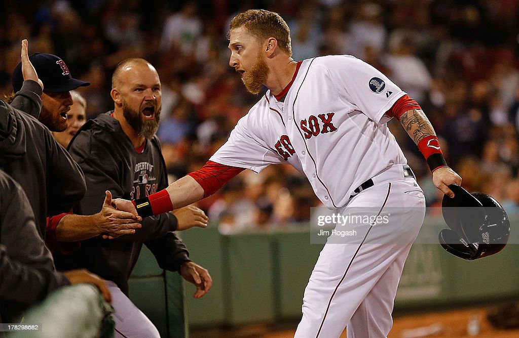 Mike Carp #37 of the Boston Red Sox celebrates with teammates after knocking in the go-ahead run in the 8th inning against the Baltimore Orioles at Fenway Park on August 28, 2013 in Boston, Massachusetts.
