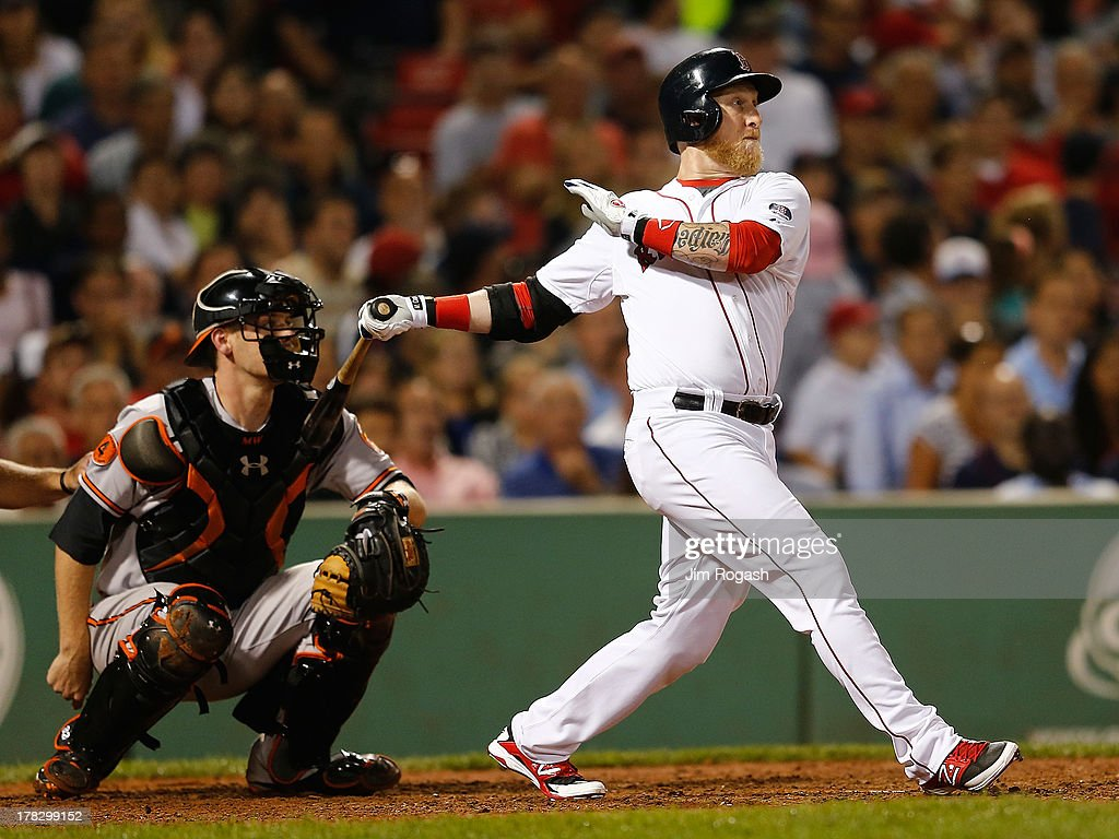 Mike Carp #37 of the Boston Red Sox singles in the in the go-ahead run in the 8th inning against the Baltimore Orioles at Fenway Park on August 28, 2013 in Boston, Massachusetts. The Red Sox won 4-3.