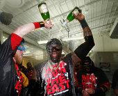 Mike Carp of the Boston Red Sox sprays David Ortiz champagne after winning the AL East Division by beating the Toronto Blue Jays at Fenway Park on...