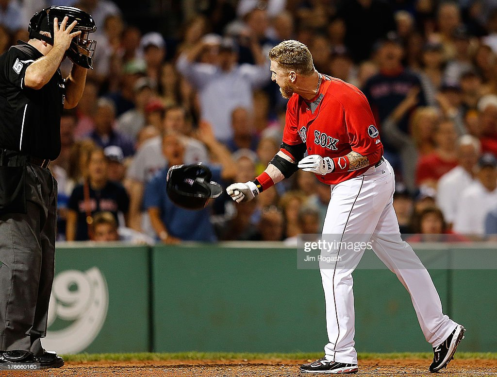 Mike Carp #37 of the Boston Red Sox throws his helmet toward umpire Bill Welke #52 after being called out on strikes in the 7th inning against the New York Yankees at Fenway Park on August 16, 2013 in Boston, Massachusetts.