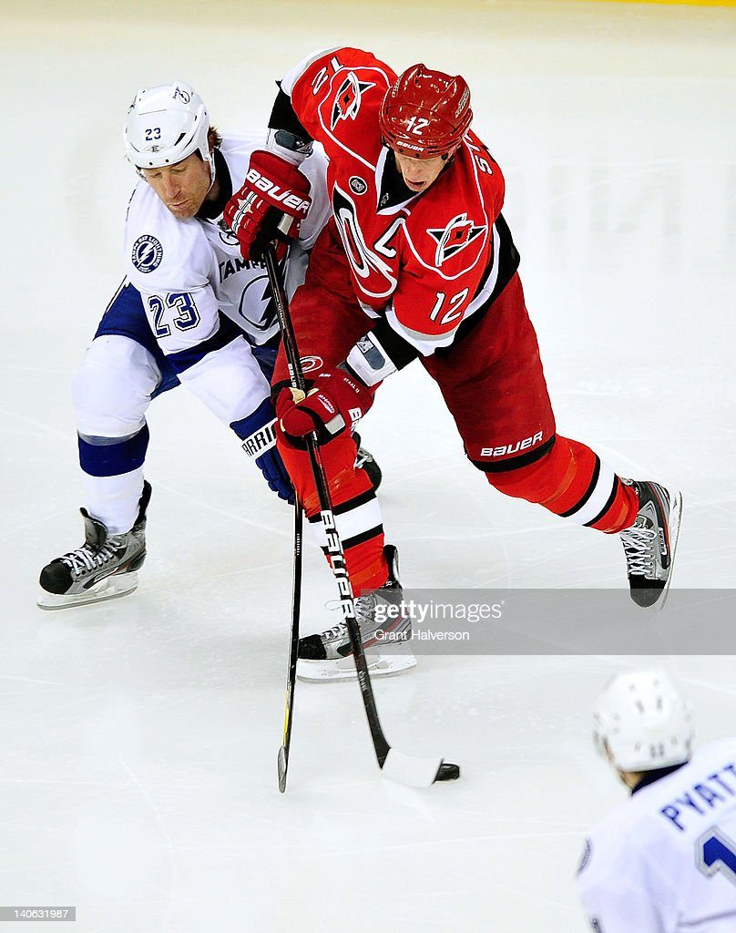 <a gi-track='captionPersonalityLinkClicked' href=/galleries/search?phrase=Mike+Commodore&family=editorial&specificpeople=214225 ng-click='$event.stopPropagation()'>Mike Commodore</a> #23 of the Tampa Bay Lightning vies for the puck with <a gi-track='captionPersonalityLinkClicked' href=/galleries/search?phrase=Eric+Staal&family=editorial&specificpeople=202199 ng-click='$event.stopPropagation()'>Eric Staal</a> #12 of the Carolina Hurricanes during play at the RBC Center on March 3, 2012 in Raleigh, North Carolina. The Lightning won 4-3 in overtime.