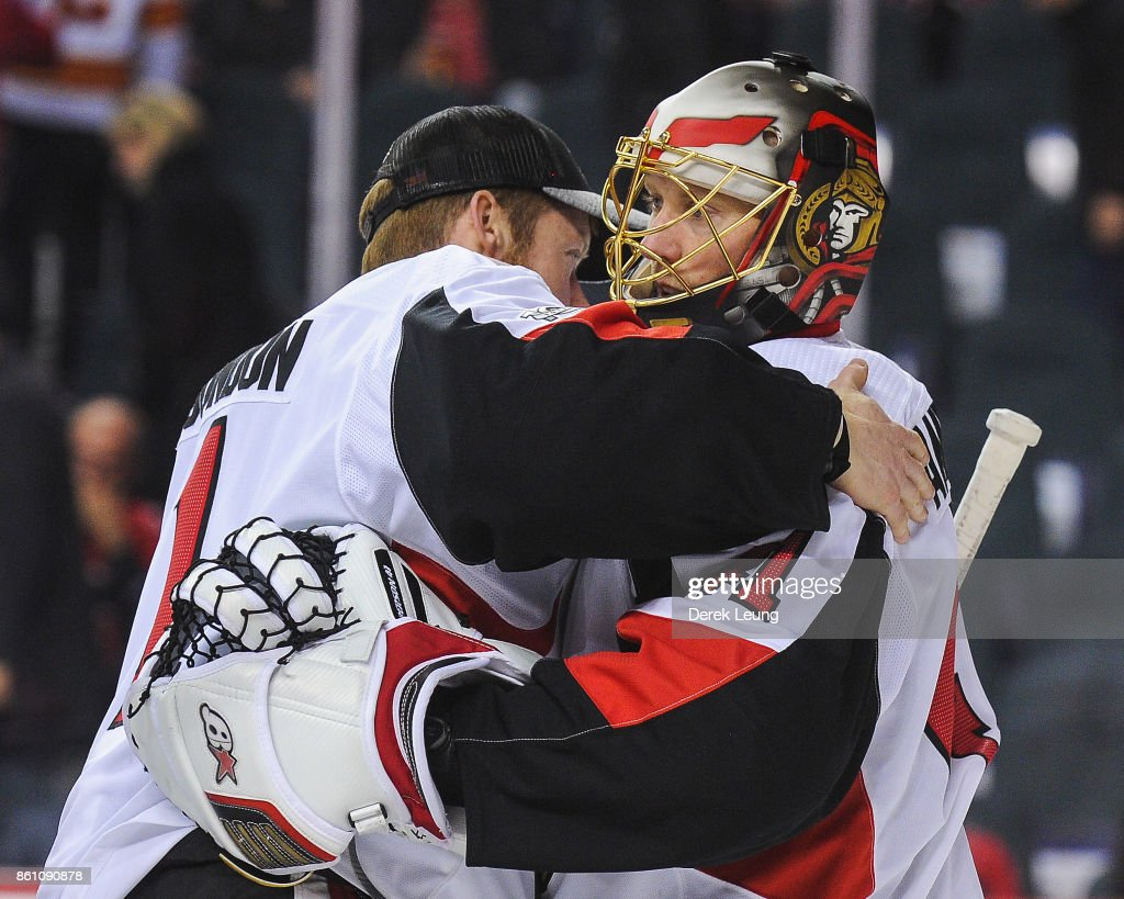 Mike Condon #1 (L) congratulates Craig Anderson #41 of the Ottawa Senators after defeating the Calgary Flames 6-0 during an NHL game at Scotiabank Saddledome on October 13, 2017 in Calgary, Alberta, Canada.