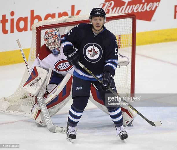 Mike Condon of the Montreal Canadiens looks around Marko Dano of the Winnipeg Jets in third period action in an NHL game at the MTS Centre on March 5...